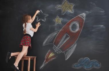 ילדה מציירת חללית אדומה בגיר על לוח עם כוכבים