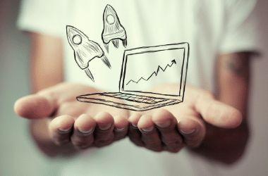 ידיים של אישה עם ציור של מחשב נייד עליו גרף עם שתי חלליות טסות לשמיים